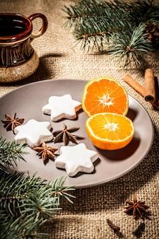 シナモン、スターアニス、コーン付きの天然モミの木の枝、荒布にコーヒーを入れたプレート上の星型のジンジャーブレッドクッキー。色調効果。