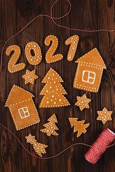 Пряники в виде цифр на новый 2021 год с другим рождественским печеньем на деревянном столе