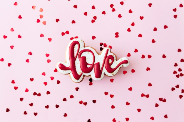 진저 쿠키는 붉은 심장 반짝임을 좋아합니다. 발렌타인 데이 카드. 분홍색 배경. 고품질 사진