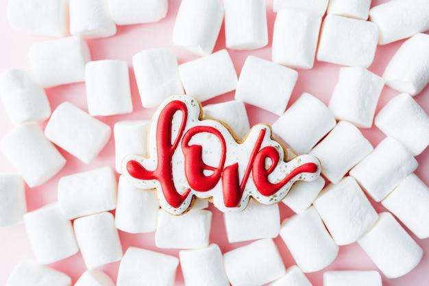 진저 브레드 쿠키는 흰색 마시멜로를 좋아합니다. 발렌타인 데이 카드. 분홍색 배경. 고품질 사진
