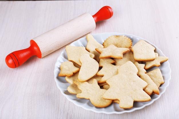 나무 테이블에 구리 쿠키 커터와 롤링 핀이 있는 접시에 진저브레드 쿠키