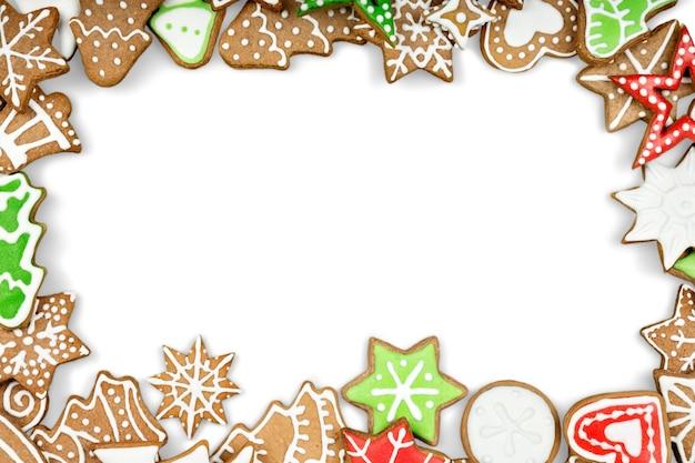 白い背景の上のジンジャーブレッドクッキー。スノーフレーク、星、男、天使、キャンディーの形