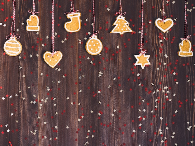 Gingerbread cookies on rope for christmas tree decoration new year on wooden table