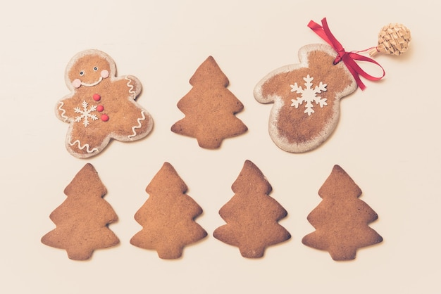 Gingerbread cookies in the shape of christmas trees, man and mittens on a white background. top view