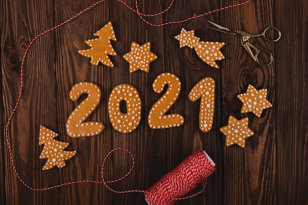 Gingerbread cookies in the shape of the numbers for the new year 2021 with other christmas cookies on a wooden table