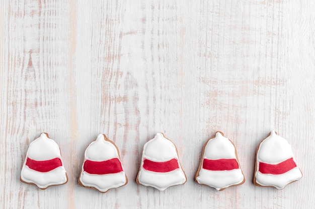 Gingerbread cookies shaped bell ring on a bright textured wooden background