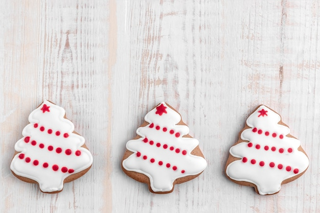 Gingerbread cookies shaped christmas tree on a bright textured wooden background