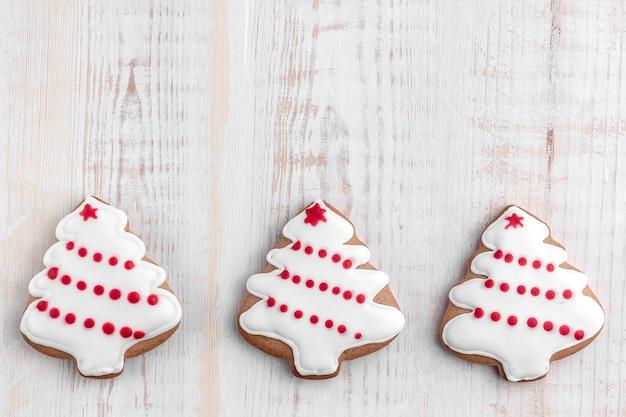 ジンジャーブレッドクッキーは、明るい質感の木製の背景にクリスマスツリーを形作った