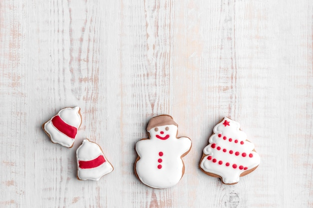 Gingerbread cookies shaped christmas tree, snowman and bell ring on a bright textured wooden background