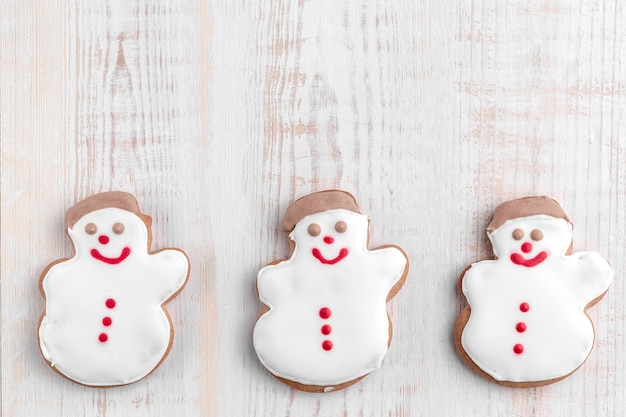 Gingerbread cookies shaped snowman on a bright textured wooden background