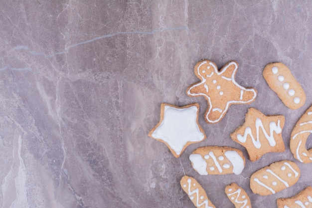 Gingerbread cookies in star, stick and ovale shapes on marble.