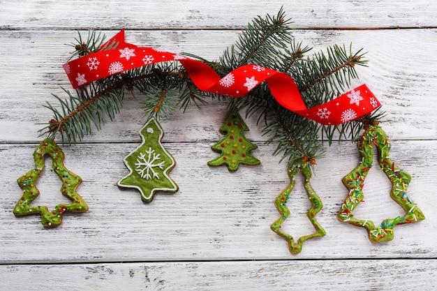 Пряники с рождественским украшением на фоне цветного деревянного стола