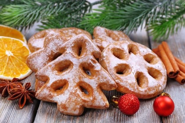 木製のテーブルの背景にクリスマスの装飾とジンジャーブレッドクッキー