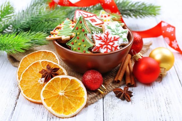 컬러 나무 테이블에 오렌지 조각과 크리스마스 장식이 있는 진저브레드 쿠키