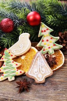 木製のテーブルの背景にオレンジとクリスマスの装飾のスライスとジンジャーブレッドクッキー