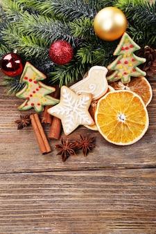 나무 테이블 표면에 오렌지 조각과 크리스마스 장식이 있는 진저브레드 쿠키
