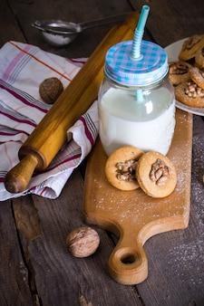 テーブルの上にクルミとミルクのカップとジンジャーブレッドクッキー
