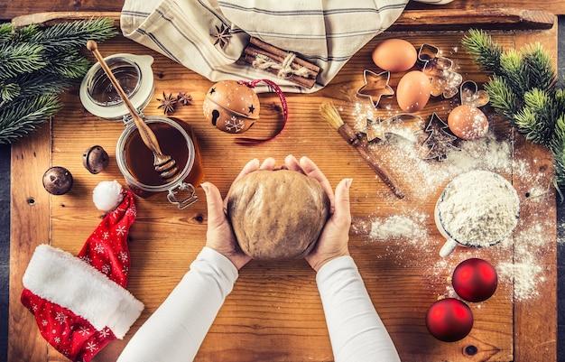진저브레드 반죽과 크리스마스 비스킷 케이크를 준비하는 여자 손.