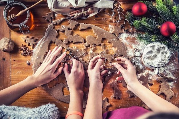 진저브레드 반죽과 어린 소녀들이 크리스마스 비스킷 케이크를 준비하고 있습니다.