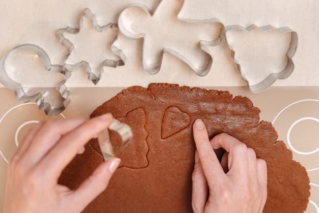 Пряничное тесто с металлическими фрезами разной формы для семейного рождественского печенья с имбирем
