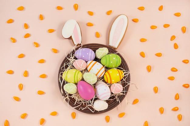 Пряники уши пасхального кролика и расписные пасхальные яйца на тарелке