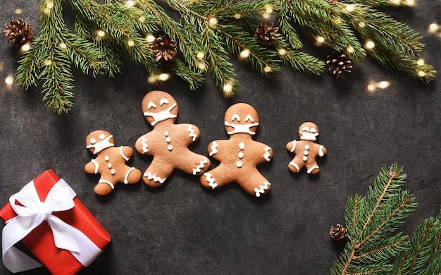 Пряничная семья в масках. новогодний фон с пряниками и подарками.