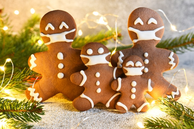 Gingerbread family in a mask.  gingerbread, spruce and lights. quarantine.