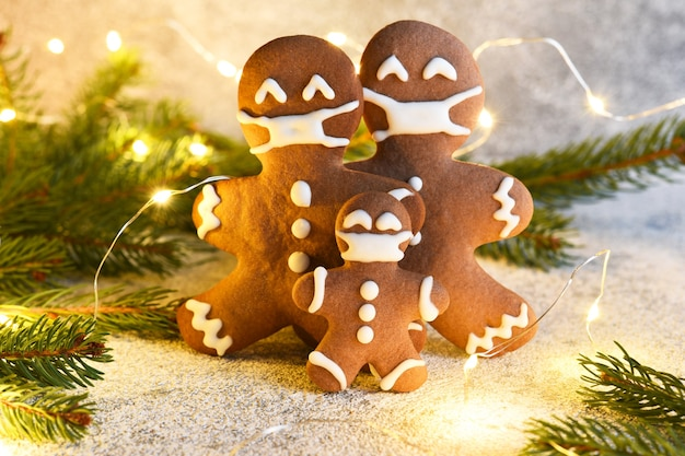 Gingerbread family in a mask. gingerbread, spruce and lights.