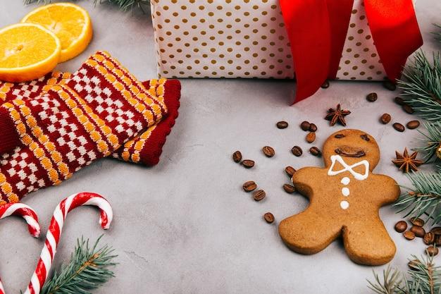 Gingerbread, fir, warm gloves, lemon, coffee beans, present box on grey floor
