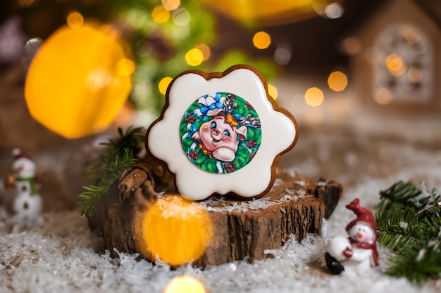 Gingerbread flower with pig portrait inside in cozy warm decoration with garland lights