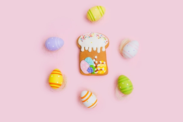 Gingerbread in the form of a cake and colorful chocolate eggs on a white wooden desk.