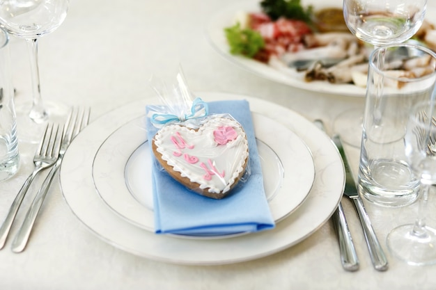 Gingerbread in form of heart lies on blue napkin on white