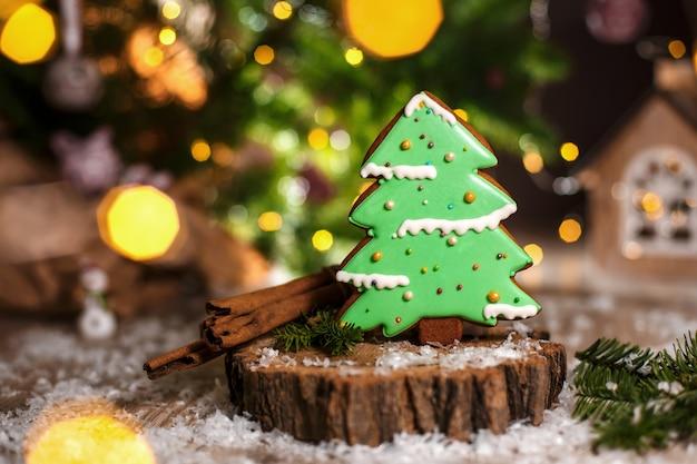 ガーランドライトと居心地の良い暖かい装飾のジンジャーブレッドグリーンクリスマスツリー