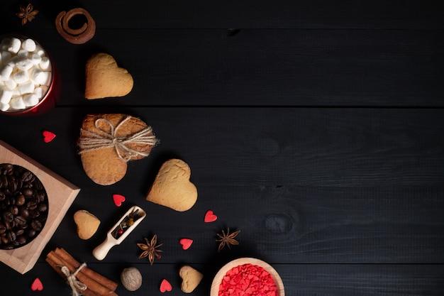 Пряники, печенье в форме сердца, специи, кофейные зерна и принадлежности для выпечки.