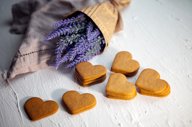 흰색 나무 테이블에 라벤더 꽃이 있는 진저브레드 하트 쿠키. 흰색 바탕에 맛 있는 수 제 하트 쿠키입니다. 발렌타인 데이 대 한 마음의 모양에 쿠키입니다. 사랑해.