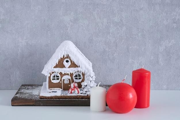 灰色の背景にジンジャーブレッドハウスとキャンドル。新年のコンセプト。メリークリスマス。
