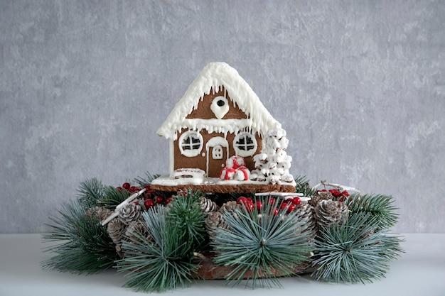 灰色の背景にジンジャーブレッドハウスとクリスマスリース。冬休み。