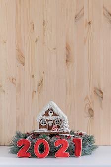 明るい木の背景にジンジャーブレッドの家と碑文2021。新年のコンセプト。コピースペース