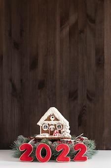 ジンジャーブレッドハウスと碑文2022。メリークリスマスの背景、コピースペース。垂直フレーム。背景の暗い木製の壁