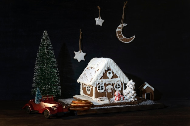 Gingerbread house and cookies next to toy car and small christmas tree. merry christmas and happy new year.