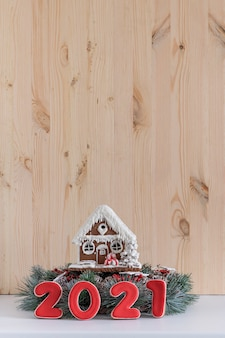 Gingerbread house and inscription 2021 on light wooden background. new year concept. copy space