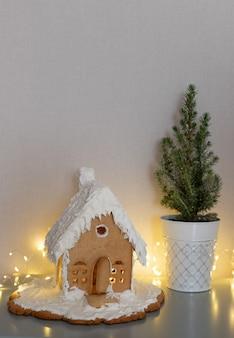 ジンジャーブレッドハウスの鉢植えのクリスマスツリーとリビングルームのきらめくライトクリスマスシーン