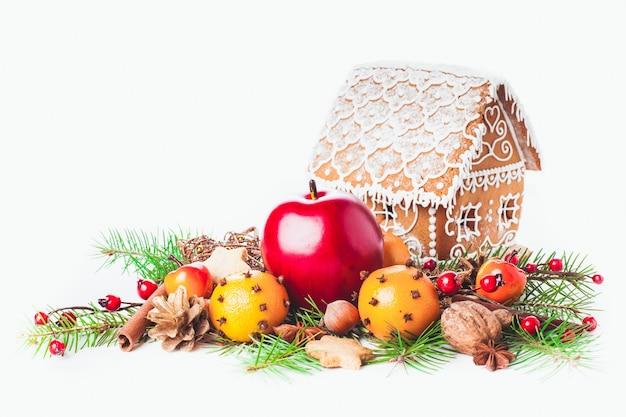 白い背景にクリスマスの装飾が施されたジンジャーブレッドハウス