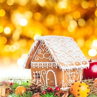 ボケ味の背景の上にクリスマスの装飾が施されたジンジャーブレッドハウス