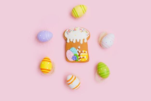 Пряники в виде торта и разноцветных шоколадных яиц на белом деревянном столе.