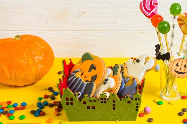 Gingerbread in little box near pumpkin and lollipop