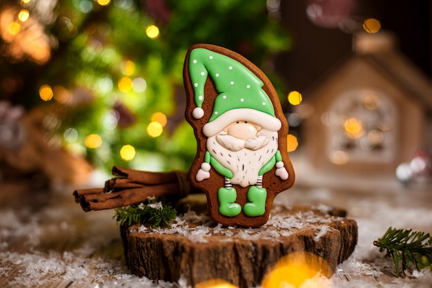 Gingerbread little fairytale gnome in cozy decoration with garland lights