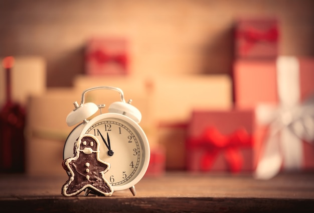 Gingerbread man and alarm clock on table with christmas gifts on background