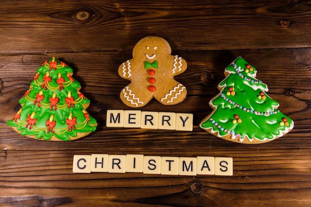 素朴な木製のテーブルにジンジャーブレッドマンとクリスマスツリー。上面図。メリークリスマスの碑文