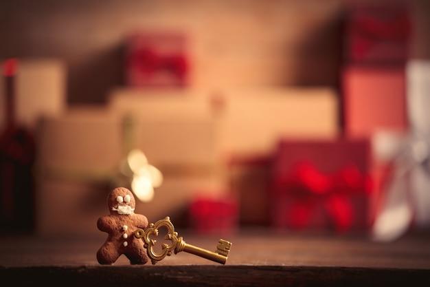 Пряничный человечек и ключ на столе с рождественскими подарками на фоне
